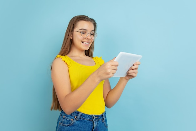 Met behulp van tablet. het portret van het kaukasische die tienermeisje op blauwe muur wordt geïsoleerd. prachtig model in casual gele slijtage. concept van menselijke emoties, gezichtsuitdrukking, verkoop, advertentie. copyspace. ziet er schattig uit, slim.