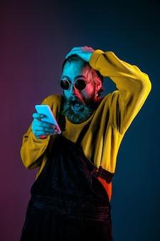 Met behulp van telefoon, extreem geschokt. kaukasisch man's portret op de achtergrond van de gradiëntstudio in neonlicht. mooi mannelijk model met hipsterstijl. concept van menselijke emoties, gezichtsuitdrukking, verkoop, advertentie.