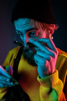 Met behulp van telefoon in zonnebril. kaukasisch man's portret op de achtergrond van de gradiëntstudio in neonlicht. mooi mannelijk model met hipsterstijl. concept van menselijke emoties, gezichtsuitdrukking, verkoop, advertentie.