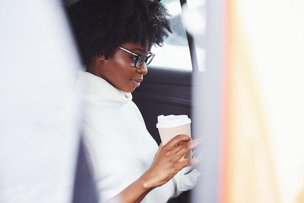 Met beker drinken. jonge afro-amerikaanse vrouw zit binnenkant van nieuwe moderne auto.