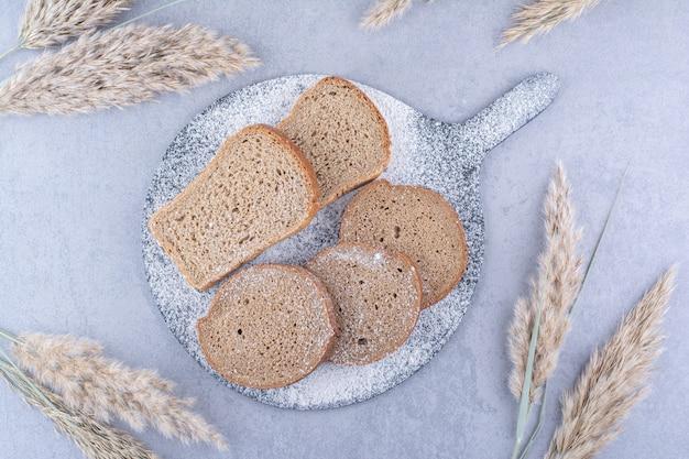 Met bloem bedekt bord met sneetjes brood naast veren grasstengels op marmeren oppervlak