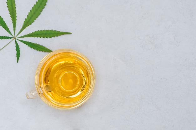 Met cannabis doordrenkte thee in een glazen beker. bovenaanzicht met kopie ruimte