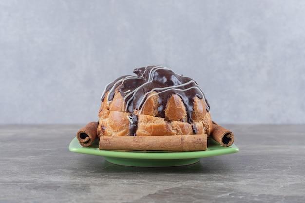 Met chocolade bedekte cake en kaneelstokjes op een kleine schaal op een marmeren oppervlak