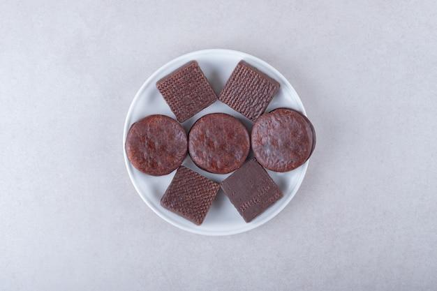 Met chocolade bedekte koekjes en wafeltje op bord, op het donkere oppervlak