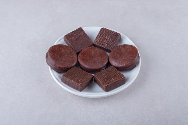 Met chocolade bedekte koekjes en wafeltje op plaat op marmeren tafel.