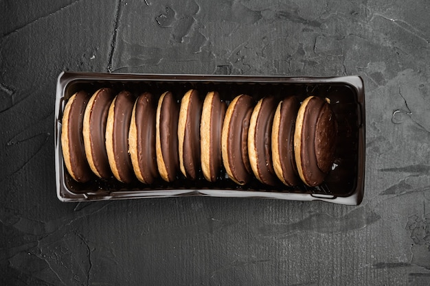 Met chocolade bedekte koekjescakes, in plastic dienbladcontainer, in plastic dienbladcontainer, op zwarte achtergrond, vlakke lay-out van het bovenaanzicht