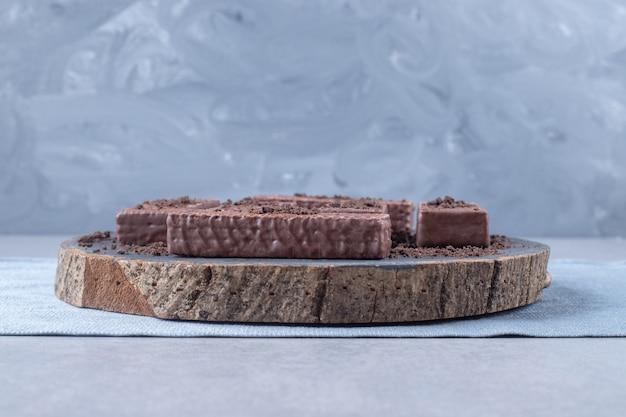 Met chocolade bedekte wafels op een houten bord op marmer