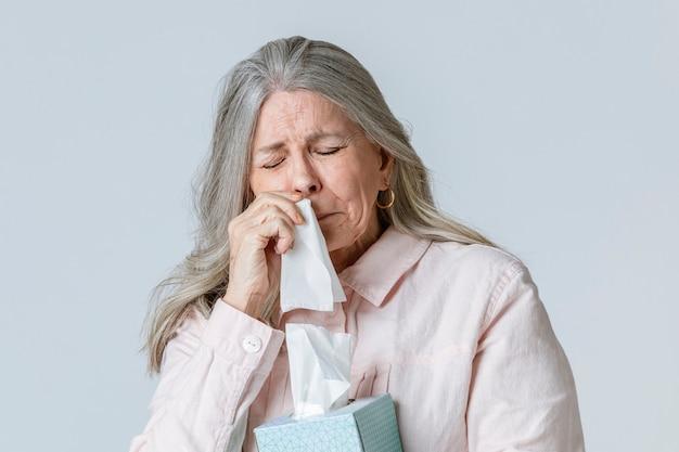 Met coronavirus geïnfecteerde oudere vrouw blaast neus in een papieren zakdoekje