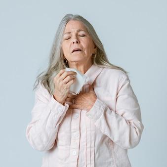 Met coronavirus geïnfecteerde oudere vrouw die niest in een papieren zakdoekje