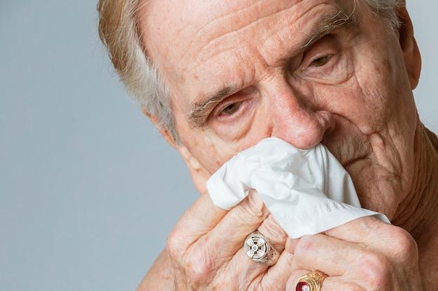 Met coronavirus geïnfecteerde senior rman snuit neus in een papieren zakdoekje