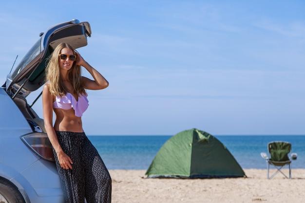 Met de auto naar zee. een meisje in een zwembroek op het strand. tent en campingstoel