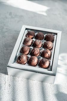 Met de hand gemaakt geassorteerde chocoladetruffelsuikergoed in doos op witte steenachtergrond
