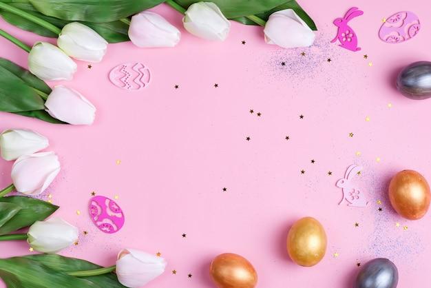 Met de hand gemaakt geschilderd ei en tulpenbloemenkader met pasen-decoratie op een lichtrose achtergrond.