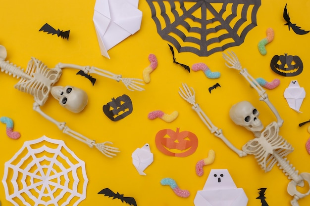 Met de hand gemaakt halloween-decor en skelet, gummy wormen op gele achtergrond. halloween-achtergrond. bovenaanzicht. plat leggen