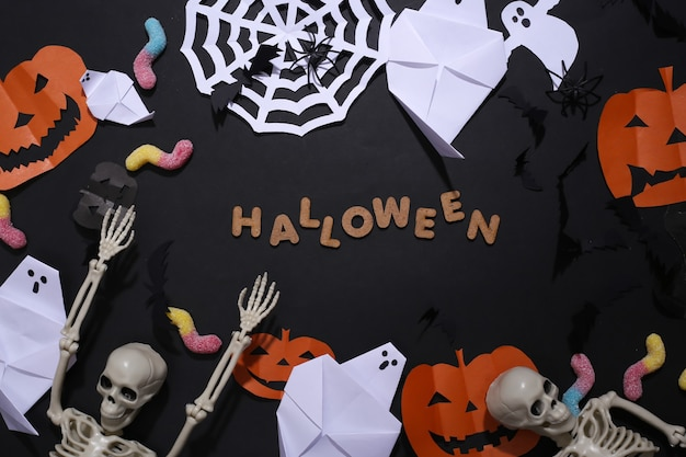 Met de hand gemaakt halloween-decor en skelet, gummy wormen op zwarte achtergrond met woord halloween. bovenaanzicht. plat leggen
