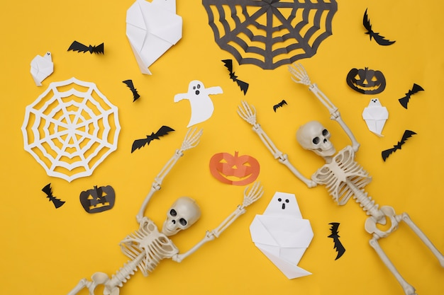 Met de hand gemaakt halloween-decor en skelet op gele achtergrond. halloween-achtergrond. bovenaanzicht. plat leggen