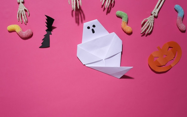 Met de hand gemaakt halloween-decor en skelethand, gummy wormen op roze achtergrond. halloween-achtergrond. bovenaanzicht. plat leggen