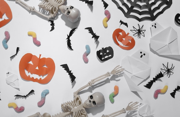 Met de hand gemaakt halloween-decor met skelet, gummy wormen op witte achtergrond. halloween-achtergrond. bovenaanzicht. plat leggen