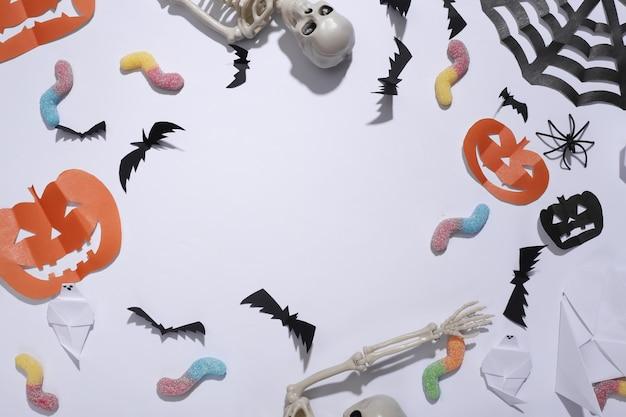 Met de hand gemaakt halloween-decor met skelet, gummy wormen op witte achtergrond. halloween-achtergrond. ruimte kopiëren. bovenaanzicht. plat leggen