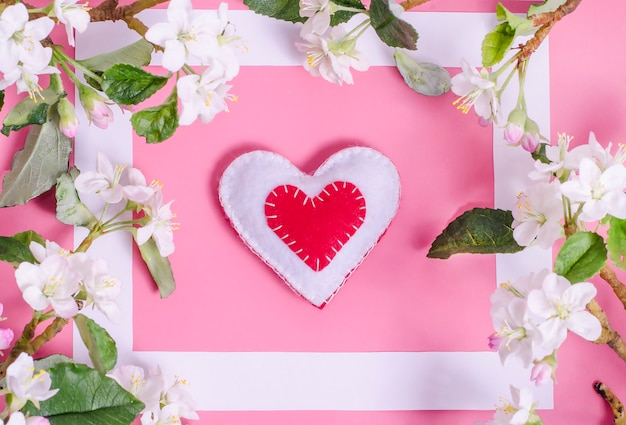 Met de hand gemaakt hart op een roze met lentebloemen.