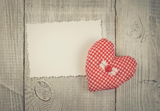 Met de hand gemaakt hart op witte houten backround. vintage zachte kleuren