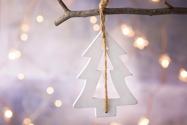 Met de hand gemaakt houten wit kerstboomornament die op tak hangen. garland lights.