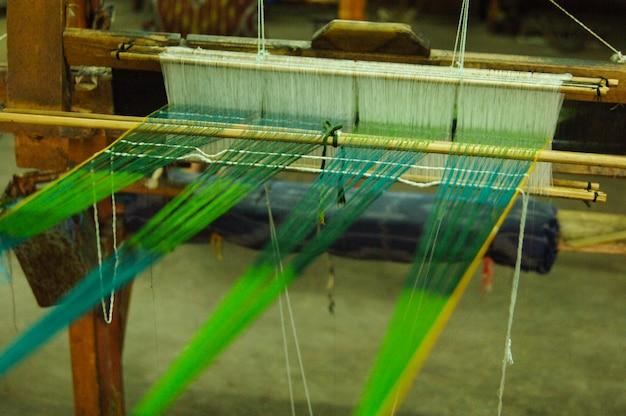 Met de hand gemaakt op een houten weefgetouw vervaardiging van draad en stof close-up