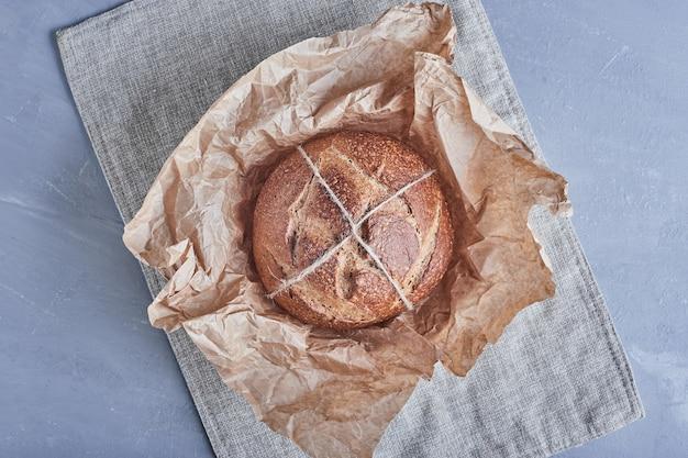 Met de hand gemaakt rond broodbroodje op de keukendoek.