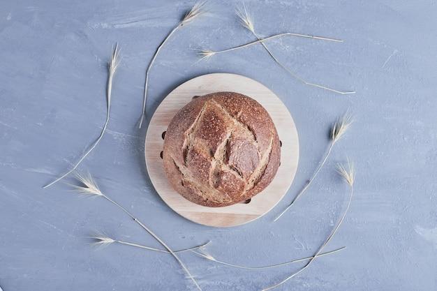 Met de hand gemaakt rond broodbroodje op een houten schotel.