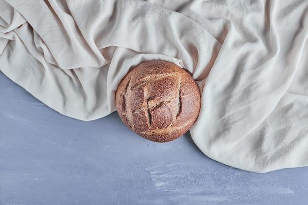 Met de hand gemaakt rond broodbroodje op grijs tafelkleed.