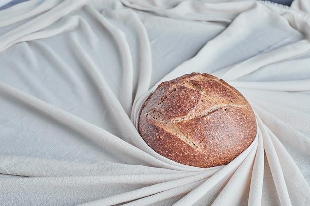 Met de hand gemaakt rond broodbroodje op het tafelkleed.
