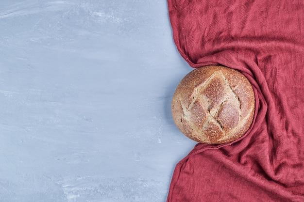 Met de hand gemaakt rond broodbroodje op rood tafelkleed.