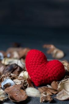 Met de hand gemaakt rood hart gemaakt van garen met gedroogde bladeren en bloem geplaatst op de zwarte houten tafel.