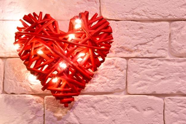 Met de hand gemaakt rood rieten decoratief hart verlicht door lichten tegen een bakstenen muurachtergrond. er is een plaats aan de rechterkant voor inscripties voor verschillende feestdagen
