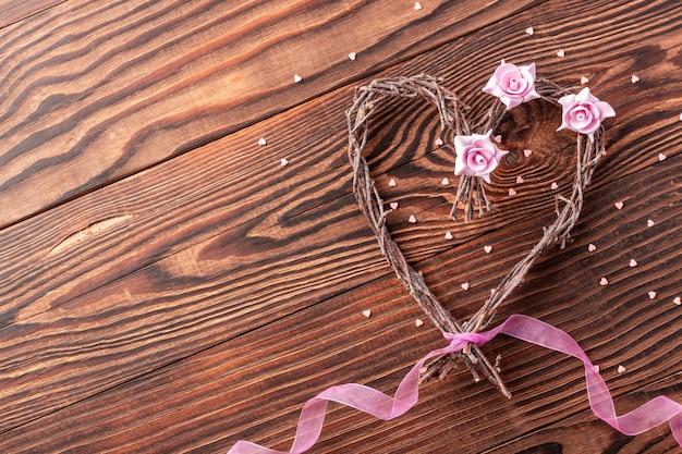 Met de hand gemaakt takkenhart met bloemen en roze lint op houten achtergrond voor huwelijk van de dag van de valentijnskaart Premium Foto