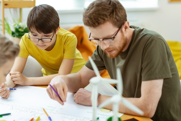 Met de hand gemaakte affiche. geconcentreerde leraar in heldere glazen met kleurrijke potloden en werken met studenten