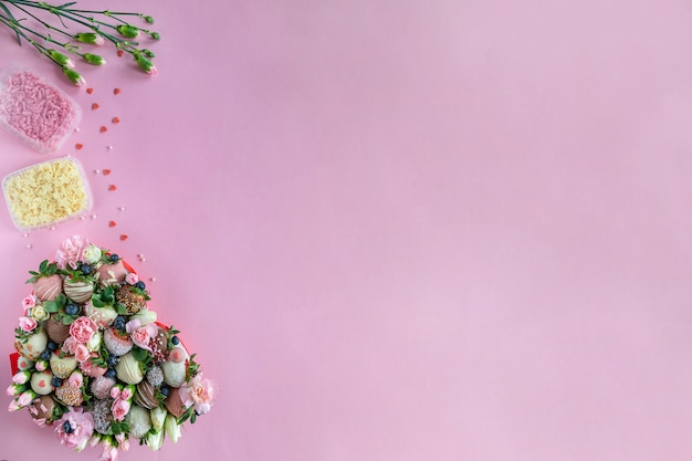 Met de hand gemaakte chocolade behandelde aardbeien, bloemen en decoratie voor het koken van dessert op roze achtergrond met vrije ruimte voor tekst
