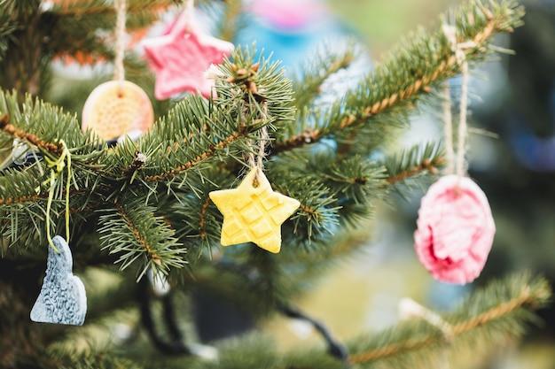 Met de hand gemaakte gebakken deegdecoratie op een openlucht kerstboom. milieu concept. selectieve aandacht, kopieer ruimte