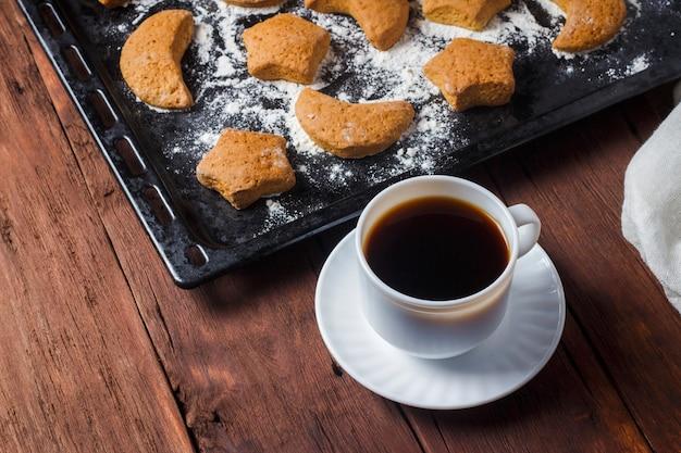 Met de hand gemaakte koekjes op een bakselblad en een kop met hete thee of koffie op een houten oppervlakte. het concept van zelfgemaakte culinaire vaardigheden.