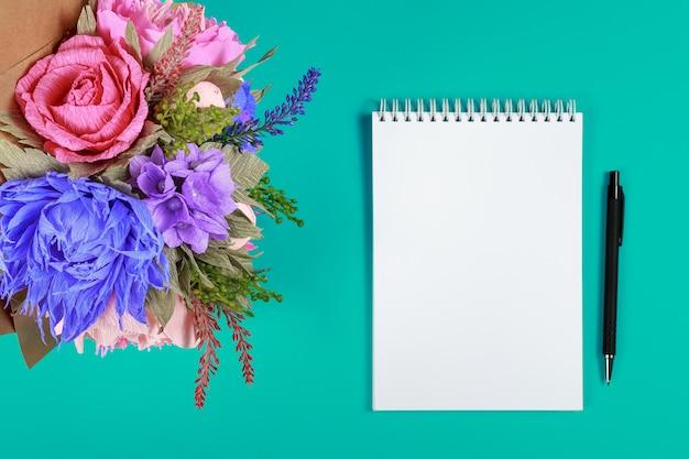 Met de hand gemaakte kunstbloemen, een notitieboekje en een zwarte pen op een blauwe achtergrond