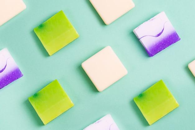 Met de hand gemaakte organische rijen van diverse kleurrijke eigengemaakte staafzepen op groen