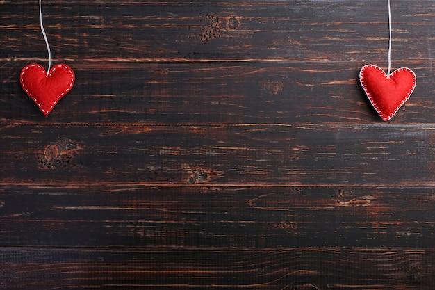 Met de hand gemaakte rode gevoelde harten, op een houten lijst, concept, banner, exemplaarruimte.