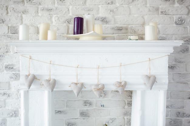 Met de hand gemaakte textiel witte harten die op een koord op witte bakstenen muur hangen