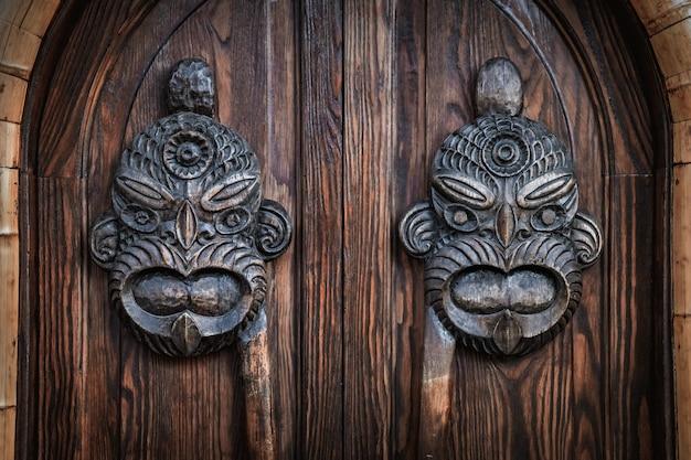 Met de hand gesneden hawaiiaanse maskers die een houten deur versieren