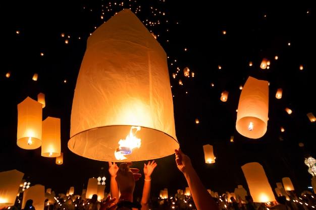 Met de hand loslaten drijvende hemel lantaarn in het traditionele thaise nieuwjaar, yi peng en loy krathong