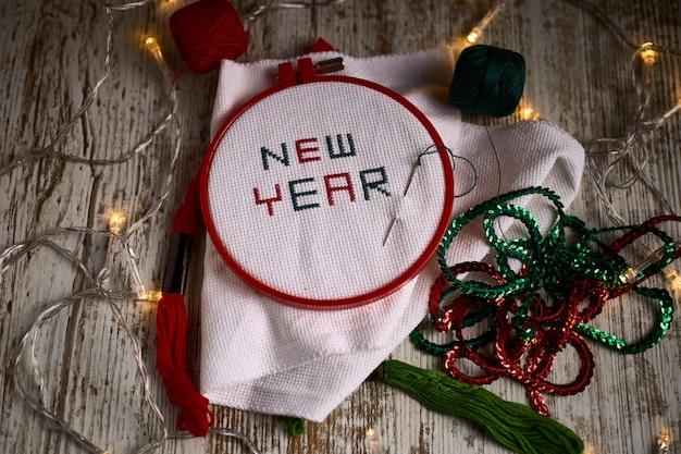 Met de hand naaien in witte taft nieuwjaar 2020 met rode en groene draden