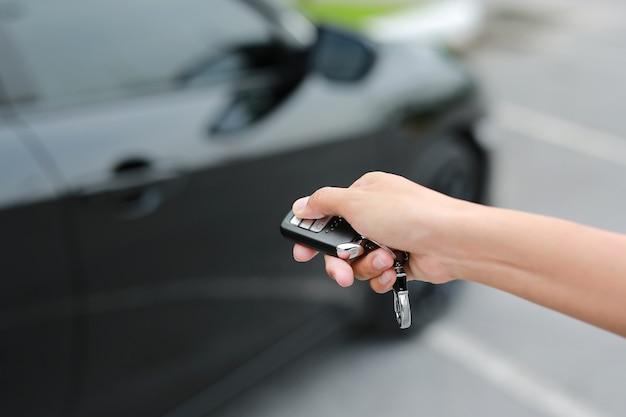 Met de hand op de knop drukken om de auto op afstand te sluiten
