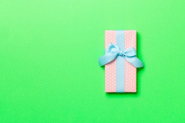 Met de hand verpakt kerstcadeau of ander vakantiecadeau in papier met blauw lint op groen, geschenkdoos, decoratie van cadeau op gekleurde tafel, bovenaanzicht