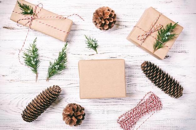 Met de hand vervaardigde geschenkdoos op rustieke witte houten met spar bovenaanzicht van de kerstmisdecoratie. afgezwakt.