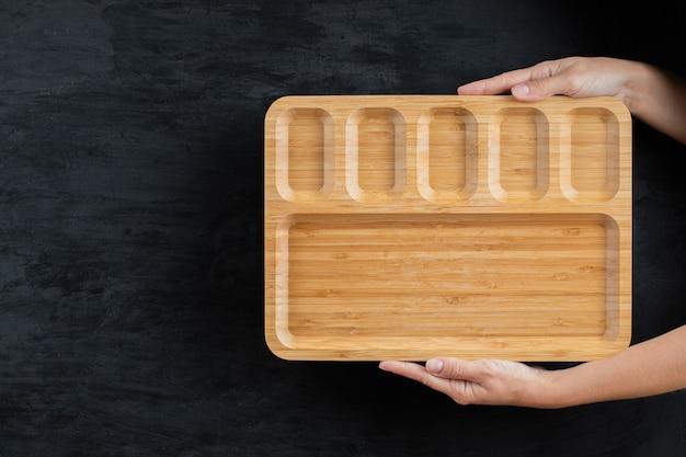 Met de handen een vierkante houten schaal vasthouden